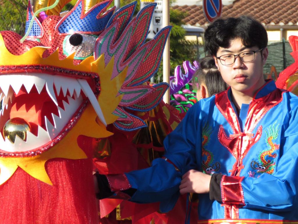 Un ragazzo tiene stretto il dragone rosso in piazza del Mercato Nuovo