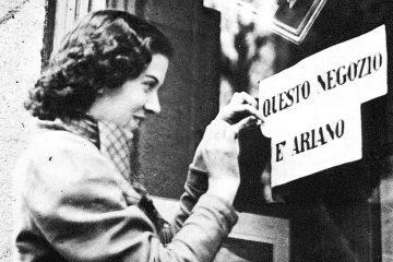 """Leggi razziali, una ragazza appone il cartello """"questo negozio è ariano"""""""