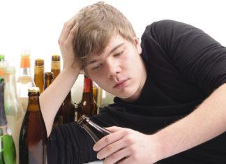Un ragazzo circondato da bottiglie di birra vuote