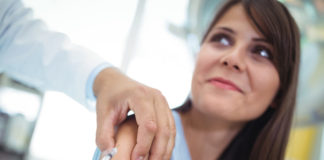Medico inietta il vaccino contro l'influenza a una paziente