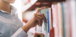 Ragazza in biblioteca cerca un libro