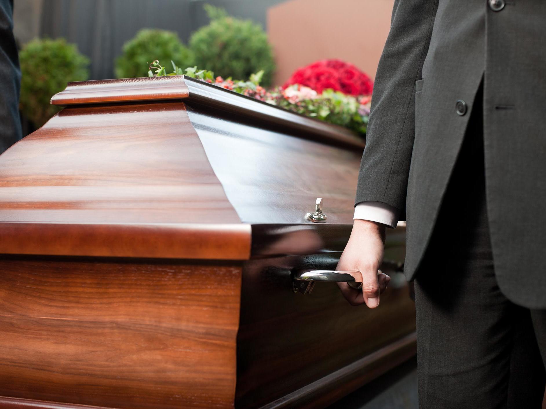 Pompe funebri: un operatore prende una bara durante un funerale