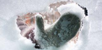 Una mano pulisce la neve dal parabrezza