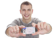 Giovane sorridente mostra la patente