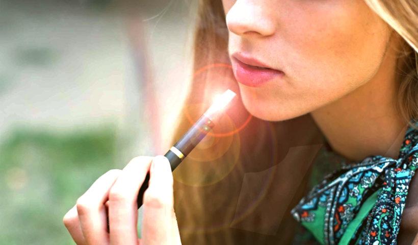 Ragazza fuma sigaretta elettronica alla nicotina