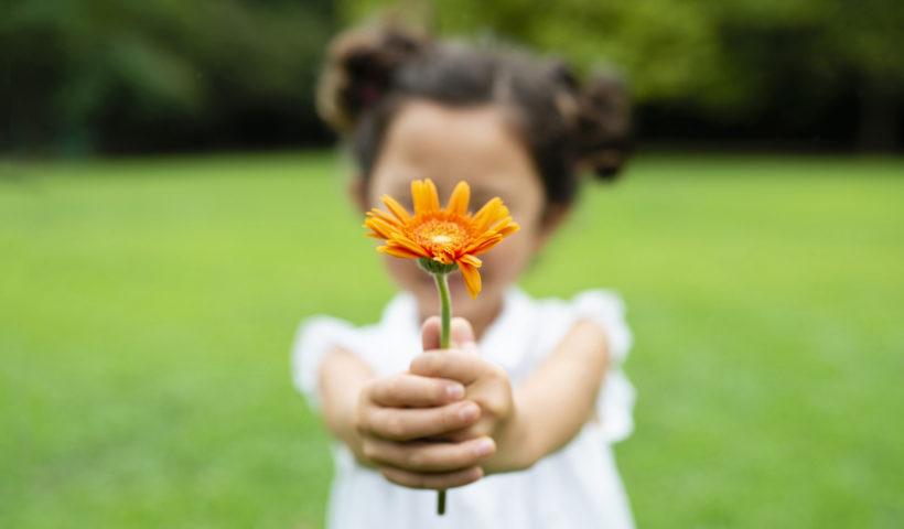Bambina con un fiore a primavera