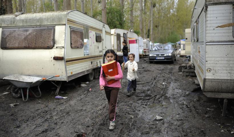Bambine con i libri di scuola in un campo rom