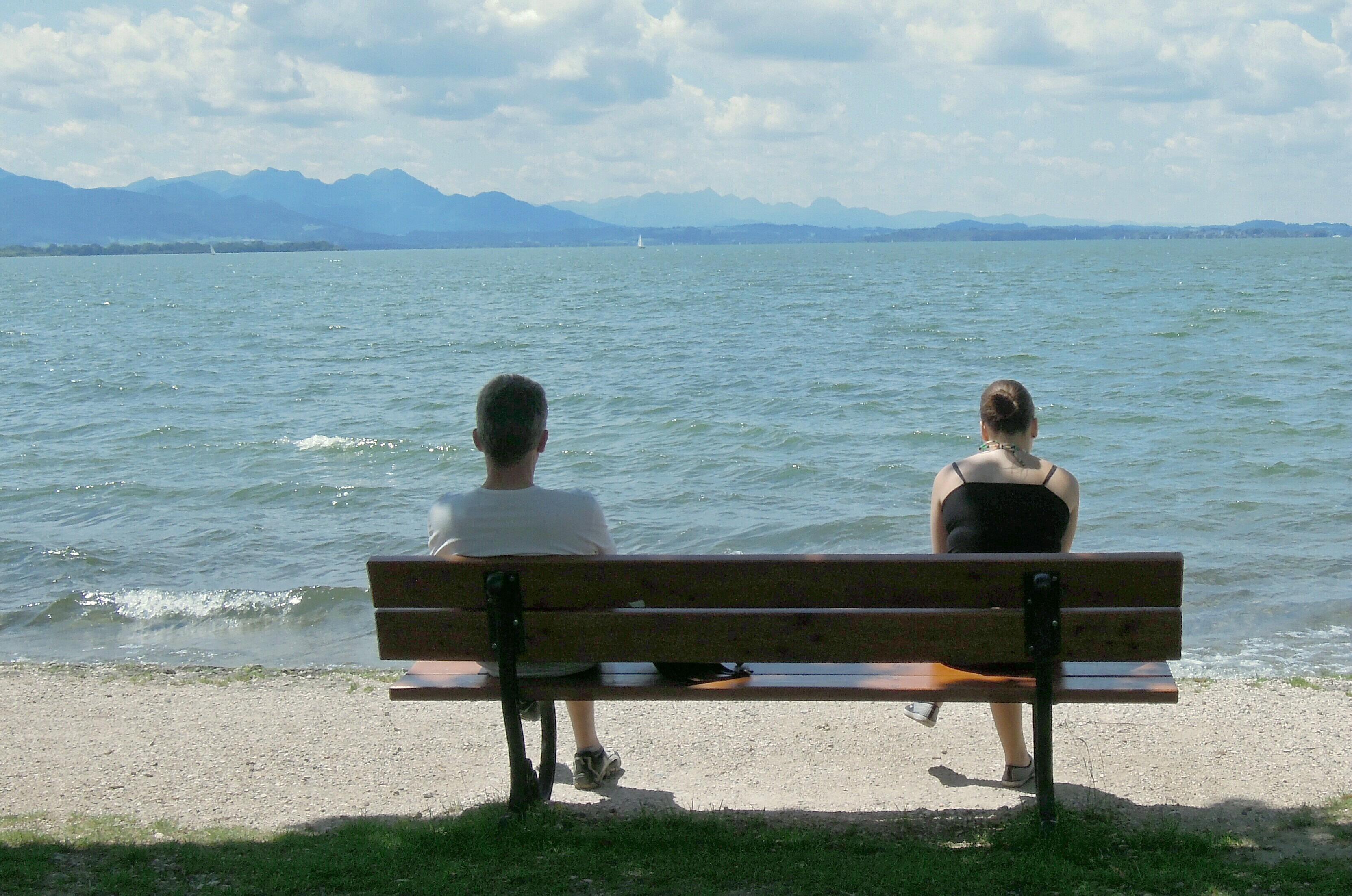 Una coppia si lascia, seduta su una panchina davanti al mare