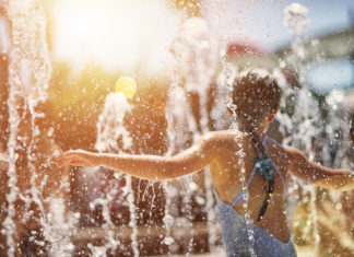 Una bambina si rinfresca in una fontana pubblica
