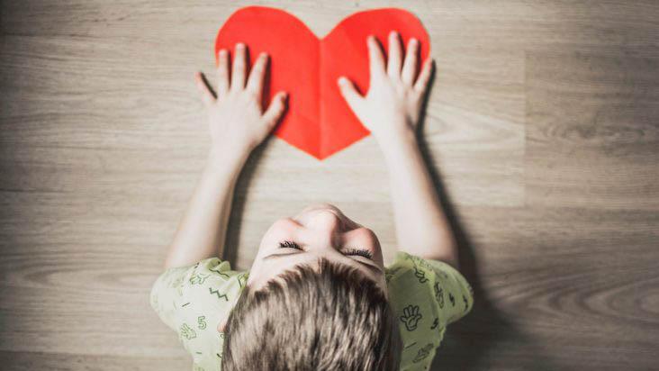 Bambino con mani su cuore disegnato