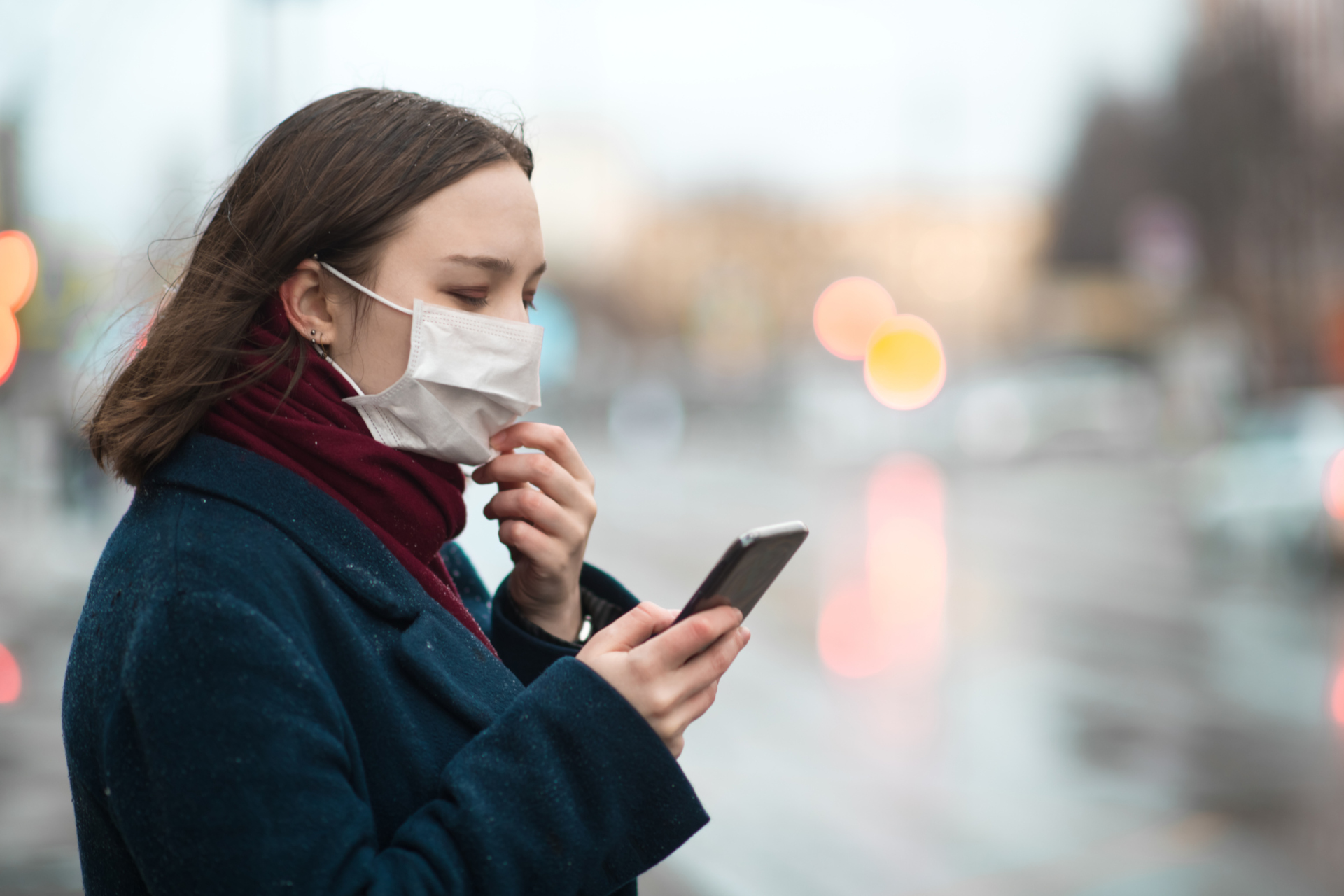 Ragazza con la mascherina e lo smartphone