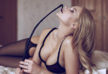 Donna sexy con frustino si pone come dominante in una relazione Bdsm