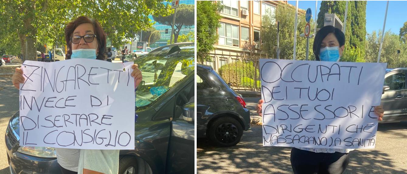 Due manifesanti con i cartelloni rivolti al presidente della Regione Lazio Nicola Zingaretti