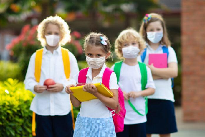 Bambini con la mascherina e i libri