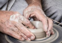 Mani su un vaso in terracotta in produzione