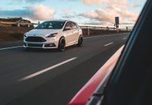 white car driving on asphalt freeway