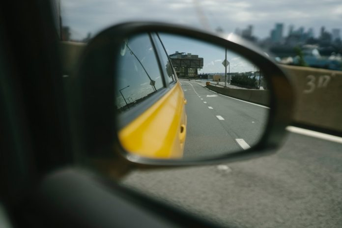 reflection of city road in side mirror