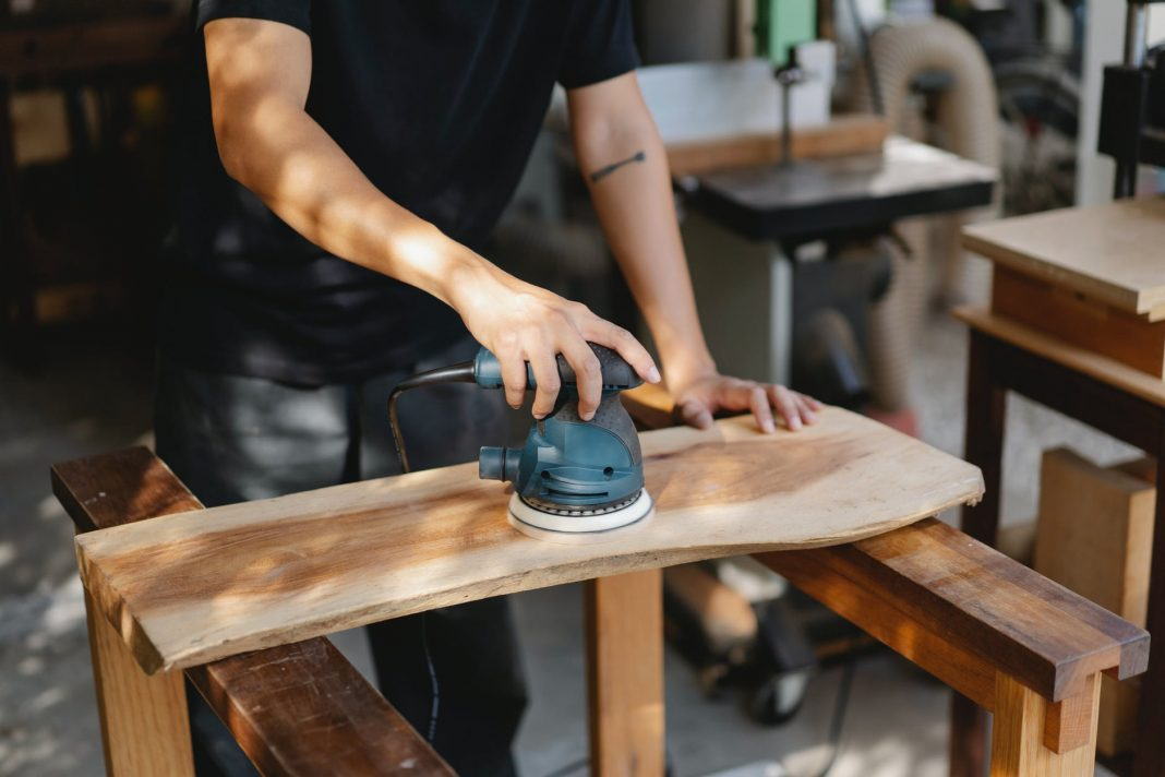 craftsman polishing wooden board with grinding instrument